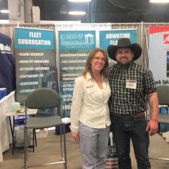 woman and man wearing cowboy hat in front of a trade show display