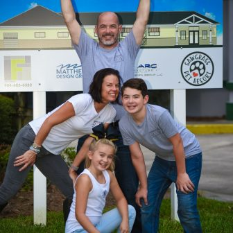 family posing in front of sign
