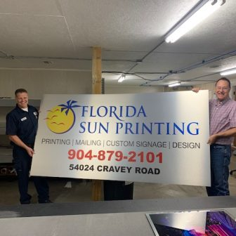 Two men holding a Florida Sun Printing banner