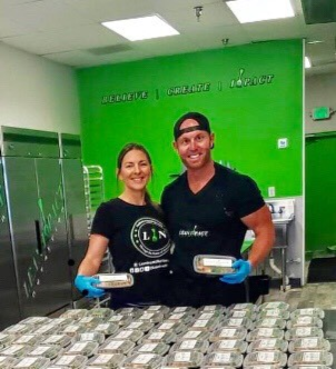 Two business owners in front of pre-packaged meals